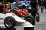 Guests wander past racing cars at the 2012 PRI show.